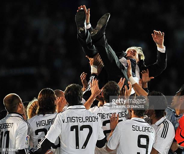 Real Madrid's German coach Bernd Schuster is thrown in the air after Real won the Spanish league title at the Santiago Bernabeu stadium in Madrid on...