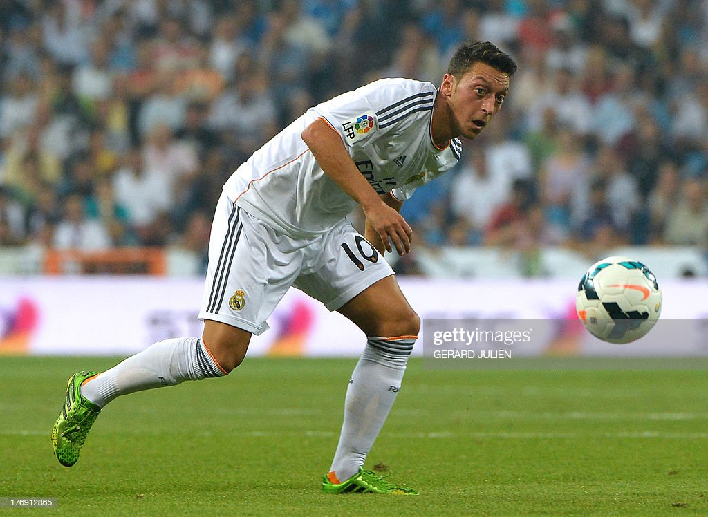 Real Madrid's German midfielder Mesut Ozil eyes the ball during the Spanish league football match Real Madrid CF vs Real Betis at the Santiago Bernabeu stadium in Madrid on August 18, 2013. Real Madrid won 2-1.
