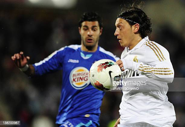 Real Madrid's German midfielder Mesut Ozil vies with Getafe's defender Miguel Torres during their Spanish league football match between Getafe and...