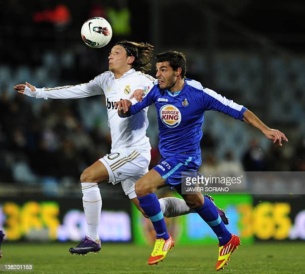 Real Madrid's German midfielder Mesut Ozil vies with Getafe's defender Miguel Torres during their Spanish league football match Getafe against Real...