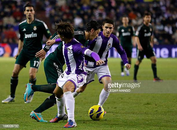 Real Madrid's German midfielder Mesut Ozil vies with Valladolid's midfielders during the Spanish league football match Real Valladolid CF vs Real...