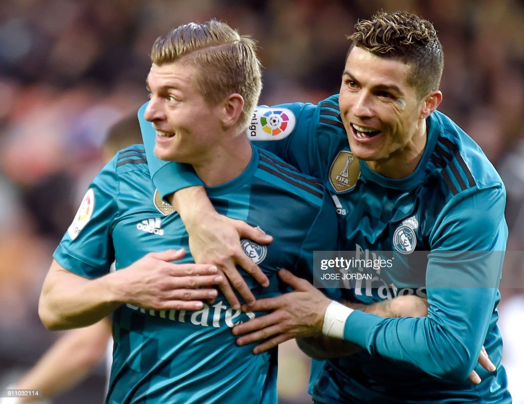 Real Madrid's German midfielder Toni Kroos (L) celebrates a goal with Real Madrid's Portuguese forward Cristiano Ronaldo during the Spanish league football match between Valencia CF and Real Madrid CF at the Mestalla stadium in Valencia on January 27, 2018. /