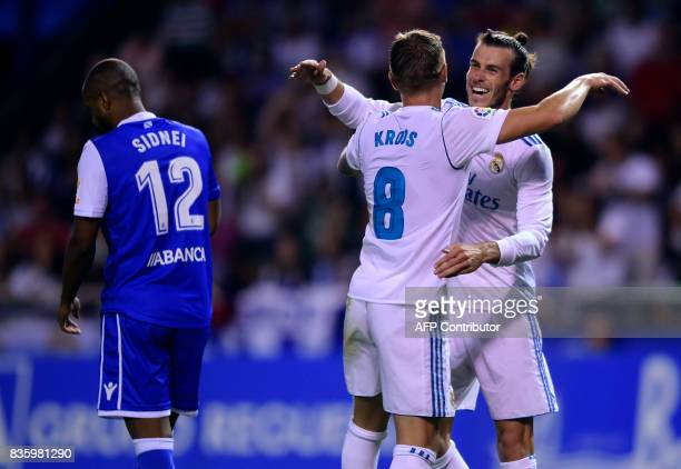 Real Madrid's German midfielder Toni Kroos celebrates with teammate Welsh forward Gareth Bale next to Deportivo La Coruna's Brazilian defender Sidnei...