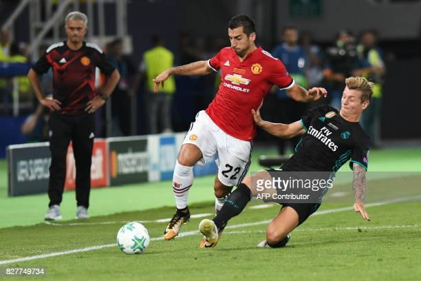 Real Madrid's German midfielder Toni Kroos tackles Manchester United's Armenian midfielder Henrikh Mkhitaryan during the UEFA Super Cup football...