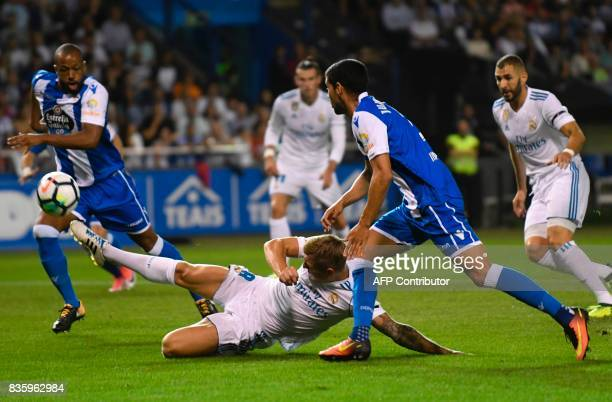 Real Madrid's German midfielder Toni Kroos tries to score a goal next to Deportivo La Coruna's Brazilian defender Sidnei during the Spanish league...