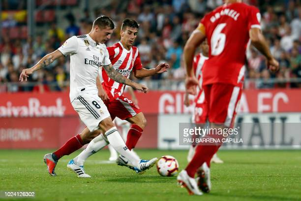 Real Madrid's German midfielder Toni Kroos vies with Girona's Spanish midfielder Pere Pons during the Spanish league football match between Girona FC...