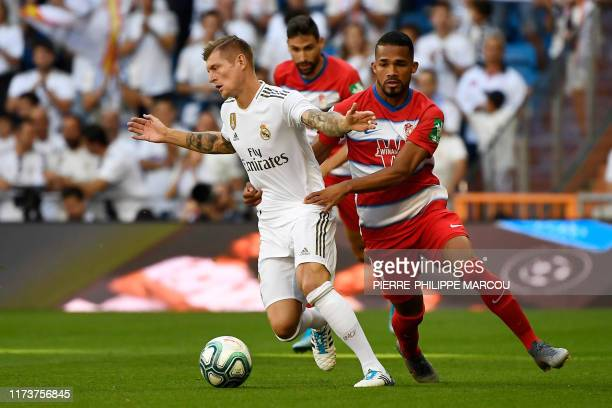 Real Madrid's German midfielder Toni Kroos vies with Granada's Venezuelan midfielder Yangel Herrera during the Spanish league football match between...