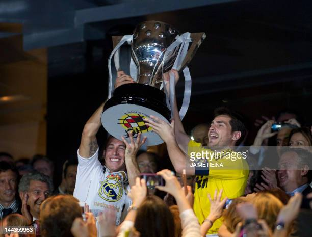 Real Madrid's goalkeeper and captain Iker Casillas and Real Madrid's defender Sergio Ramos hold the Spanish League trophy on May 13, 2012 at the...