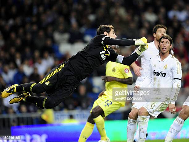 Real Madrid's goalkeeper and captain Iker Casillas dives for the ball in front of Real Madrid's defender Sergio Ramos during the Spanish League...
