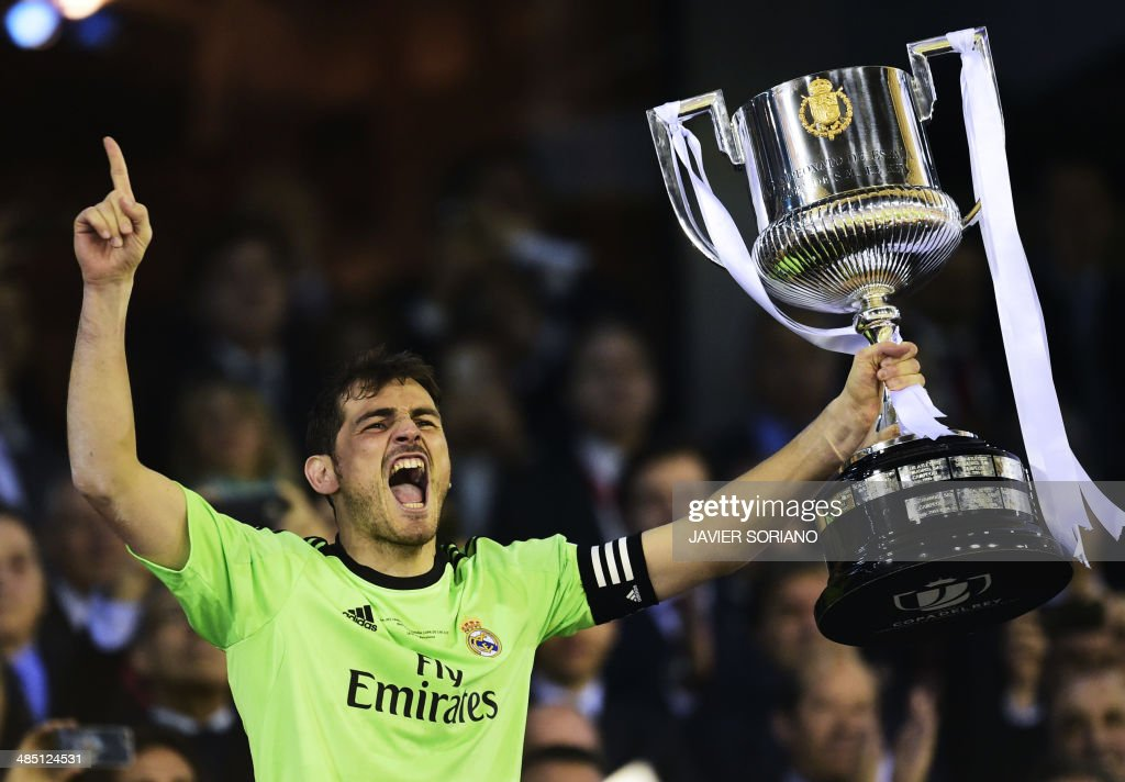 Real Madrid's goalkeeper Iker Casillas holds the trophy as he celebrates after winning the Spanish Copa del Rey (King's Cup) final 'Clasico' football match FC Barcelona vs Real Madrid CF at the Mestalla stadium in Valencia on April 16, 2014. Real Madrid won the match 2-1. AFP PHOTO/ JAVIER SORIANO / AFP PHOTO / Javier SORIANO
