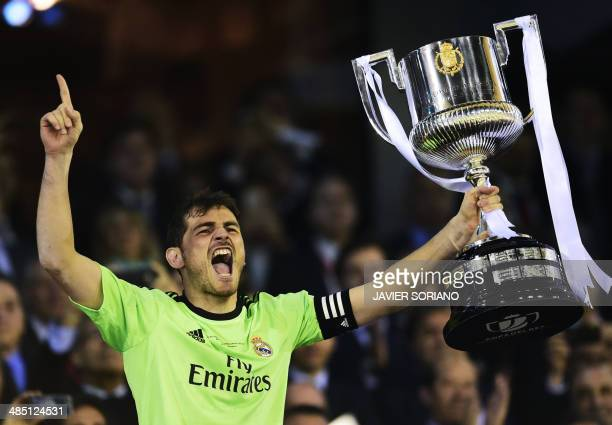Real Madrid's goalkeeper Iker Casillas holds the trophy as he celebrates after winning the Spanish Copa del Rey final 'Clasico' football match FC...