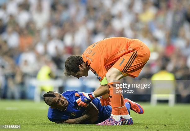Real Madrid's goalkeeper Iker Casillas touches Juventus' Chilean midfielder Arturo Vidal during the UEFA Champions League semifinal second leg...