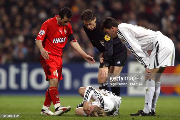Real Madrid's Guti lies in pain on the floor as his teammate Ivan Helguera , referee Lubos Michel and Monaco captain Ludovic Giuly check on his...