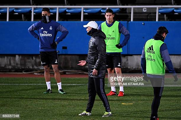 Real Madrid's head coach Zinedine Zidane instructs his players during a training session at Mitsuzawa stadium in Yokohama on December 16 ahead of...