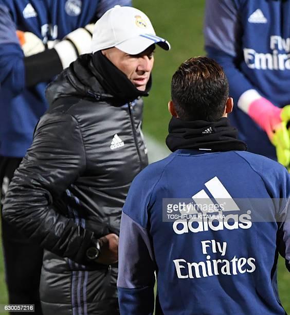 Real Madrid's head coach Zinedine Zidane speaks with forward Cristiano Ronaldo during a training session at Mitsuzawa stadium in Yokohama on December...