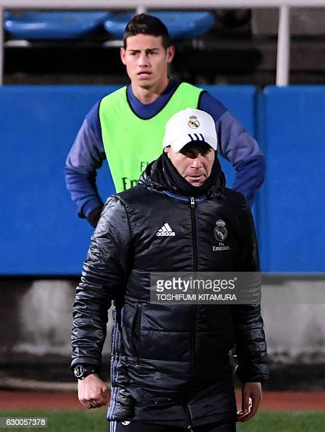 Real Madrid's head coach Zinedine Zidane walks before midfielder James Rodriguez during a training session at Mitsuzawa stadium in Yokohama on...
