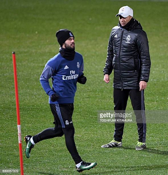 Real Madrid's head coach Zinedine Zidane watches his players during a training session at Mitsuzawa stadium in Yokohama on December 16 ahead of their...