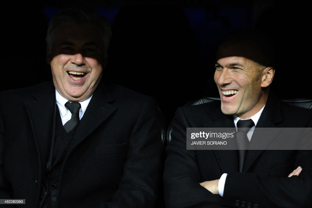 Real Madrid's Italian coach Carlo Ancelotti (L) and Real Madrid's assistant manager Zinedine Zidane laugh during the UEFA Champions League football match Real Madrid CF vs Galatasaray SK at the Santiago Bernabeu stadium in Madrid on November 27, 2013. AFP PHOTO/ JAVIER SORIANO