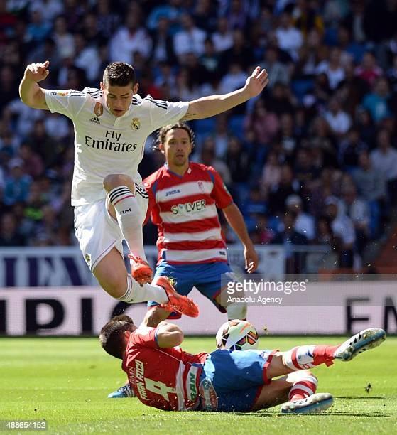 Real Madrid's James Rodriguez vies with Granada's Fran Rico during the Spanish La Liga football match between Real Madrid CF vs Granada CF at the...