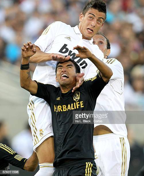 Real Madrid's Joselu and LA Galaxy player Juninho fight for control of the ball during the Herbalife World Football Challenge Friendly match between...