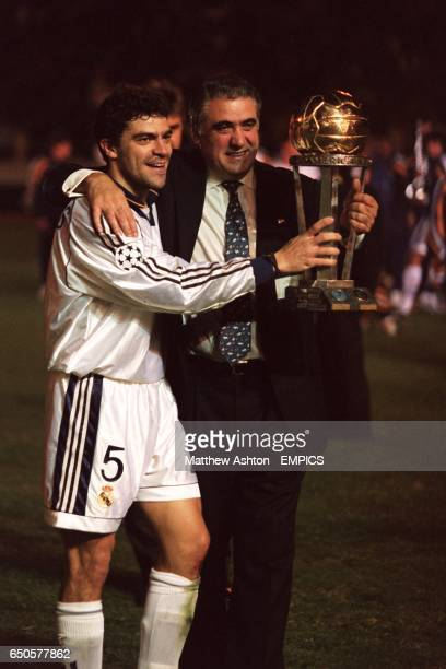 Real Madrid's Manuel Sanchis parades the World Club championship trophy with tclub president Lorenzo Sanz