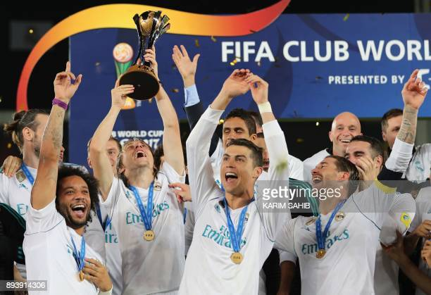 TOPSHOT Real Madrid's Marcelo Luka Modric Cristiano Ronaldo and Sergio Ramos celebrate with the FIFA Club World Cup trophy following their victory in...