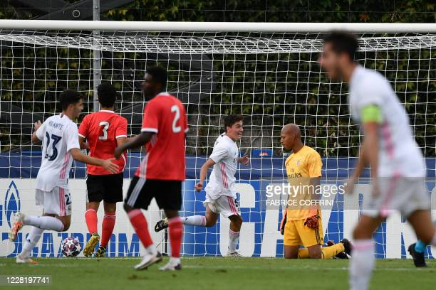 Real Madrid's midfielder Carlos Dotor celebrates the team's second goal next to Benfica's goalkeeper Leobrian Kokubo who received an own goal during...