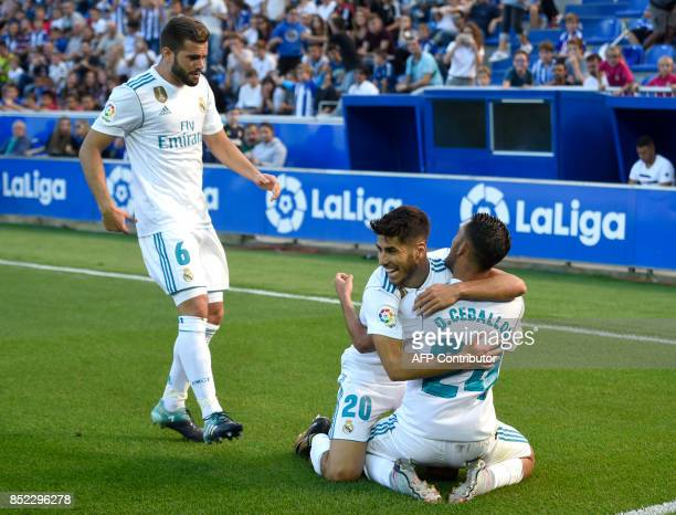 Real Madrid's midfielder from Spain Daniel Ceballos celebrates his team's second goal with teammates Real Madrid's midfielder from Spain Marco...