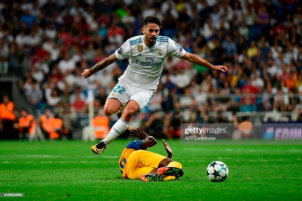 TOPSHOT - Real Madrid's midfielder from Spain Isco jumps to avoid an APOEL's player during the UEFA Champions League football match Real Madrid CF vs APOEL FC at the Santiago Bernabeu stadium in Madrid on September 13, 2017. /