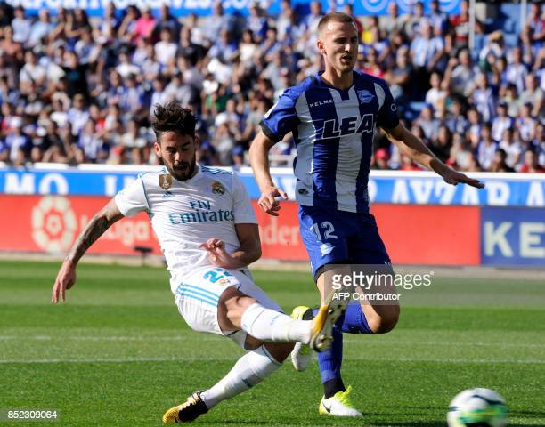 Real Madrid's midfielder from Spain Isco vies with Alaves' defender from Brazil Rodrigo Ely during the Spanish league football match Deportivo Alaves...