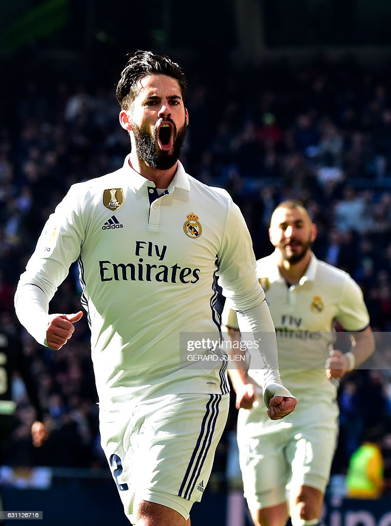 Real Madrid's midfielder Isco (L) celebrates after scoring during the Spanish league football match Real Madrid CF vs Granada FC at the Santiago Bernabeu stadium in Madrid on January 7, 2017. / AFP / GERARD