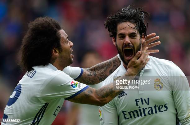 Real Madrid's midfielder Isco celebrates with teammate Brazilian defender Marcelo after scoring a goal during the Spanish league football match Real...
