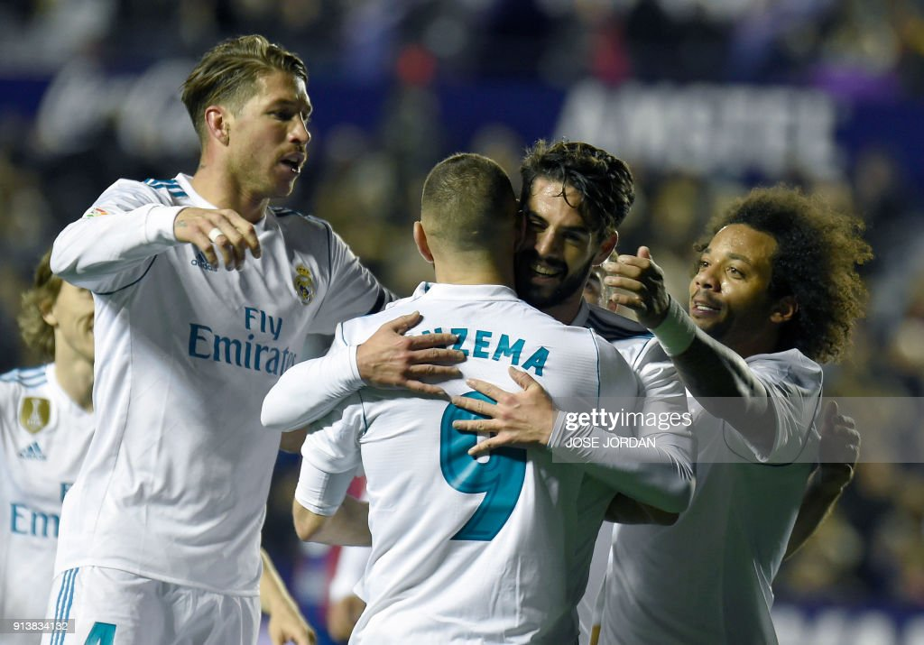 Real Madrid's midfielder Isco (C) celebrates with teammates after scoring during the Spanish league football match between Levante UD and Real Madrid CF at the Ciutat de Valencia stadium in Valencia on February 03, 2018. /