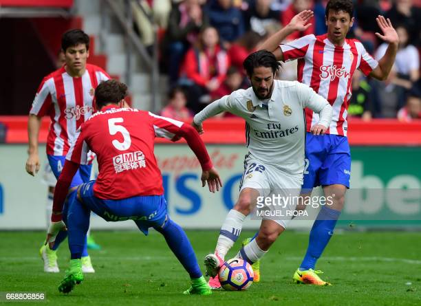 Real Madrid's midfielder Isco controls the ball next to Sporting Gijon's Venezuelan defender Fernando Amorebieta to score a goal during the Spanish...