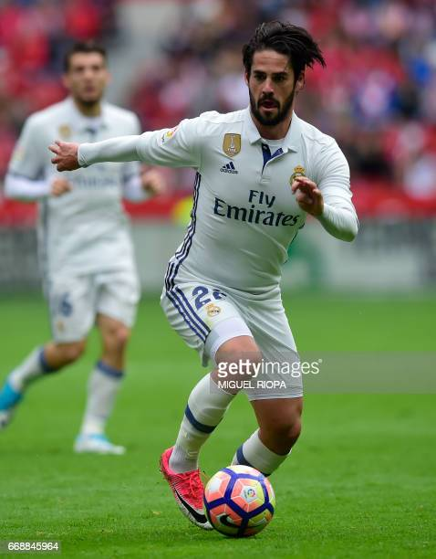 CORRECTION Real Madrid's midfielder Isco dribbles the ball during the Spanish league football match Real Sporting de Gijon vs Real Madrid CF at El...