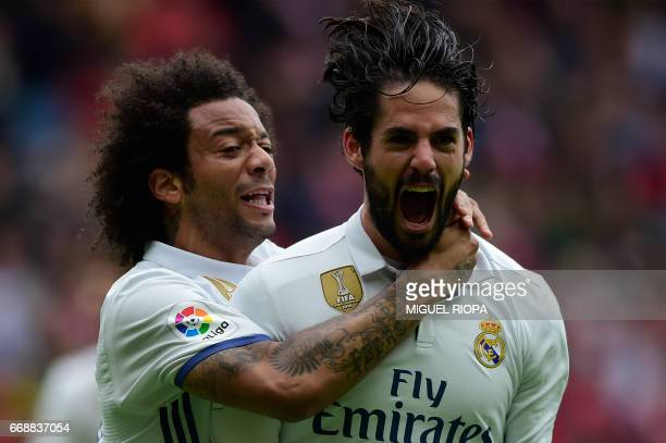 Real Madrid's midfielder Isco is congratulated by teammate Brazilian defender Marcelo after scoring a goal during the Spanish league football match...