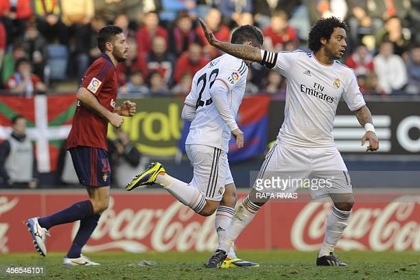 Real Madrid's midfielder Isco runs next to Real Madrid's Brazilian defender Marcelo after scoring during the Spanish league football match Osasuna vs...