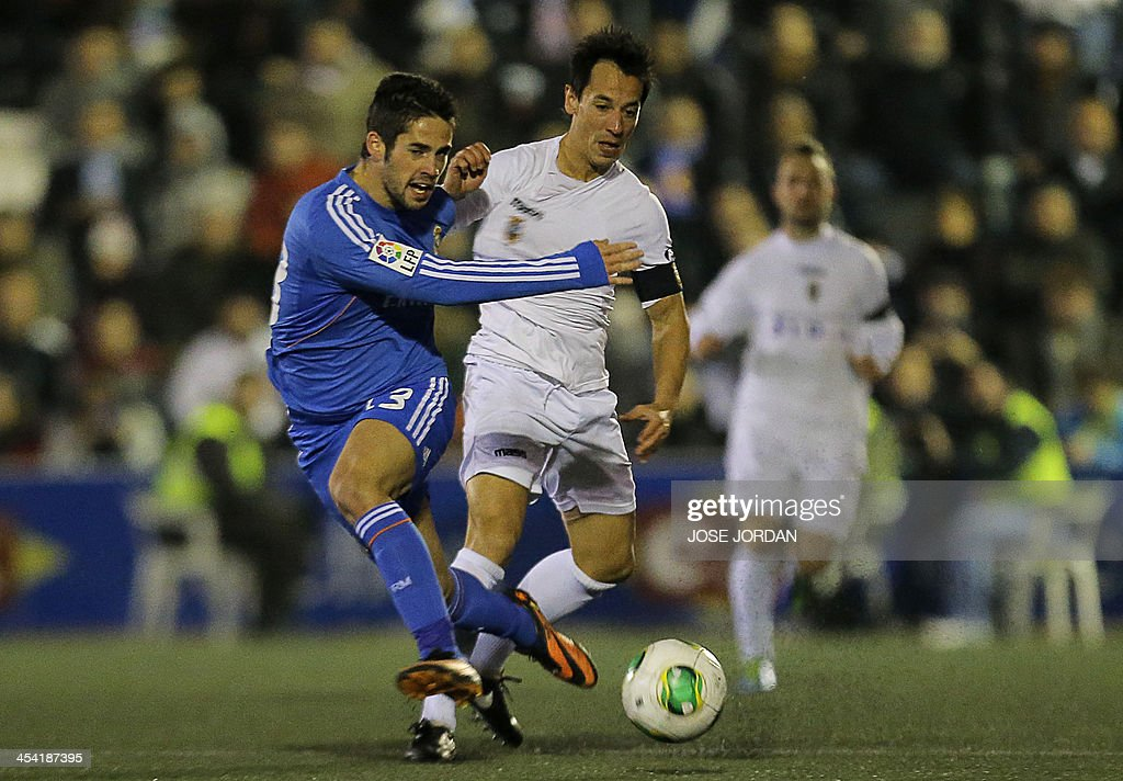 Real Madrid's midfielder Isco (L) vies with Olimpic's midfielder Rifaterra during the Spanish Copa del Rey (King's Cup) finals stage match Olimpic de Xativa vs Real Madrid CF at the La Murta stadium in Xativa on December 7, 2013.