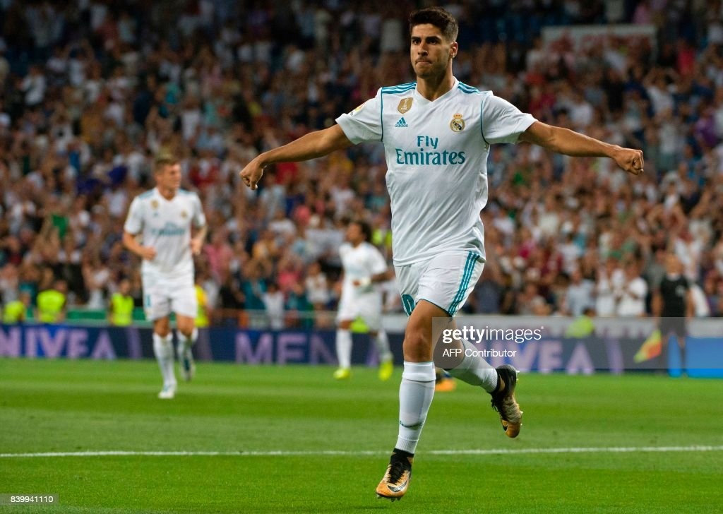 Real Madrid's midfielder Marco Asensio celebrates after scoring during the Spanish league football match Real Madrid CF vs Valencia CF at the Santiago Bernabeu stadium in Madrid on August 27, 2017. /