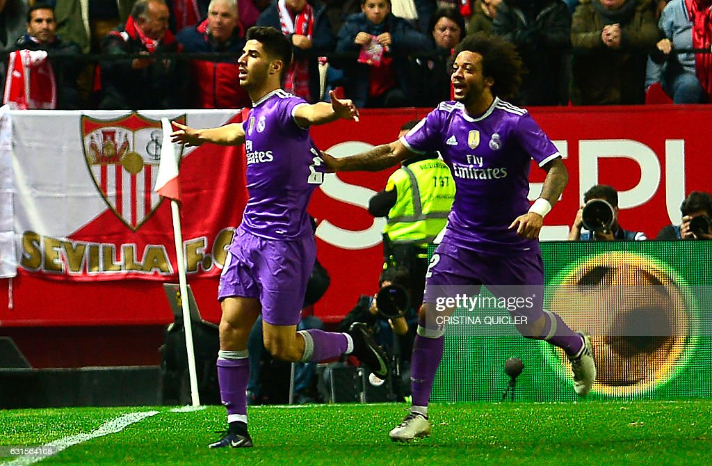 Real Madrid's midfielder Marco Asensio (L) celebrates with Real Madrid's Brazilian defender Marcelo after scoring during the Spanish Copa del Rey (King's Cup) round of 16 second leg football match Sevilla FC vs Real Madrid CF at the Ramon Sanchez Pizjuan stadium in Sevilla on January 12, 2017. / AFP / CRISTINA