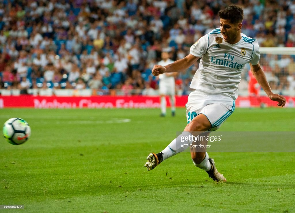 Real Madrid's midfielder Marco Asensio kicks the ball during the Spanish league football match Real Madrid CF vs Valencia CF at the Santiago Bernabeu stadium in Madrid on August 27, 2017. The game ended with a draw 2-2. /