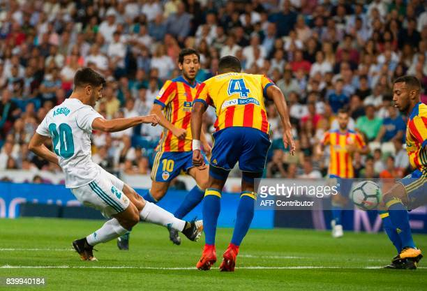 Real Madrid's midfielder Marco Asensio scores the opener during the Spanish league football match Real Madrid CF vs Valencia CF at the Santiago...