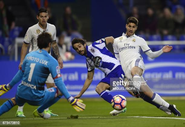 Real Madrid's midfielder Marco Asensio tries to score a goal next to Deportivo La Coruna's Argentinian goalkeeper German Dario Lux during the Spanish...