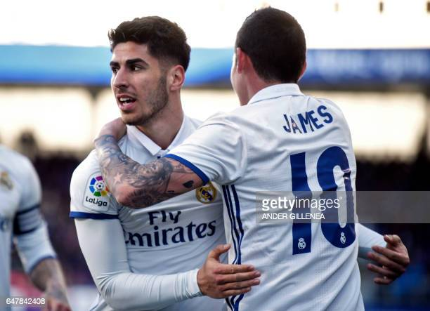 Real Madrid's midfielder Marco Asensio Willemsen celebrates with Real Madrid's Colombian midfielder James Rodriguez after scoring his team's fourth...