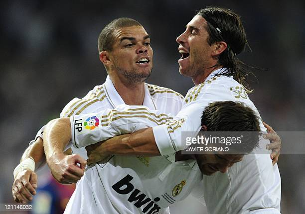 Real Madrid's midfielder Xabi Alonso celebrates with teammates Real Madrid's defender Sergio Ramos and Real Madrid's Portuguese defender Pepe after...