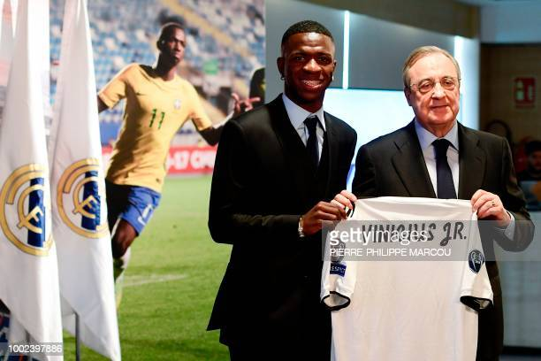 Real Madrid's new Brazilian forward Vinicius Junior holds his new jersey as he poses with Real Madrid president Florentino Perez during his official...