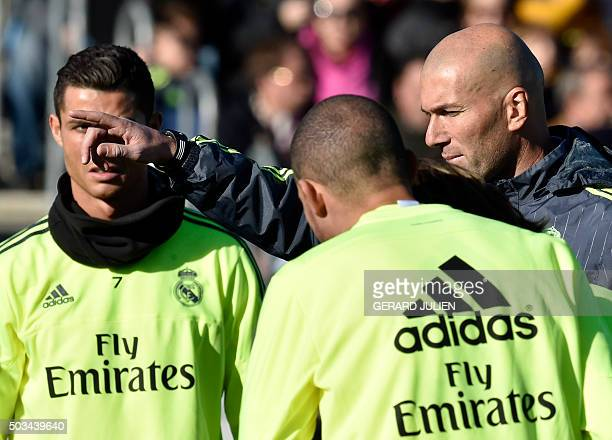 Real Madrid's new French coach Zinedine Zidane gestures past Real Madrid's Portuguese forward Cristiano Ronaldo during his first training session as...