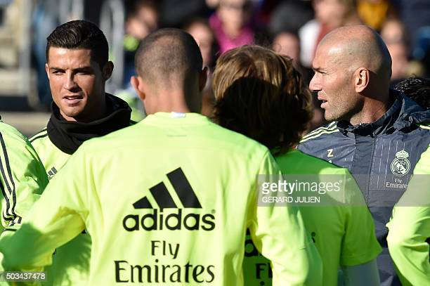 Real Madrid's new French coach Zinedine Zidane looks at Real Madrid's Portuguese forward Cristiano Ronaldo during his first training session as coach...