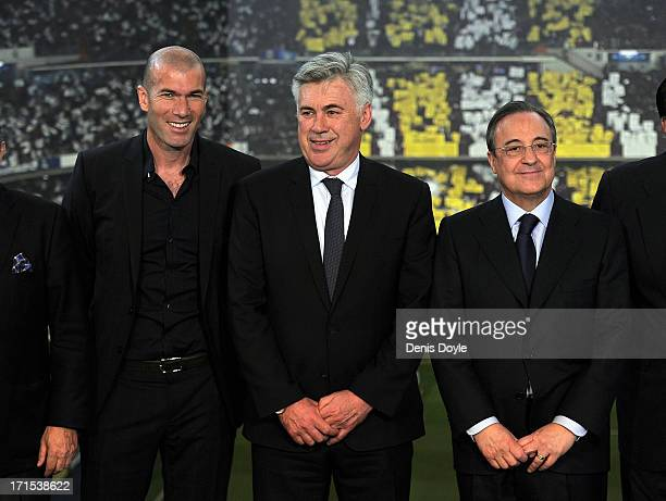 Real Madrid's new head coach Carlo Ancelotti smiles beside former Real player Zinedine Zidane and Real president Florentino Perez while being...