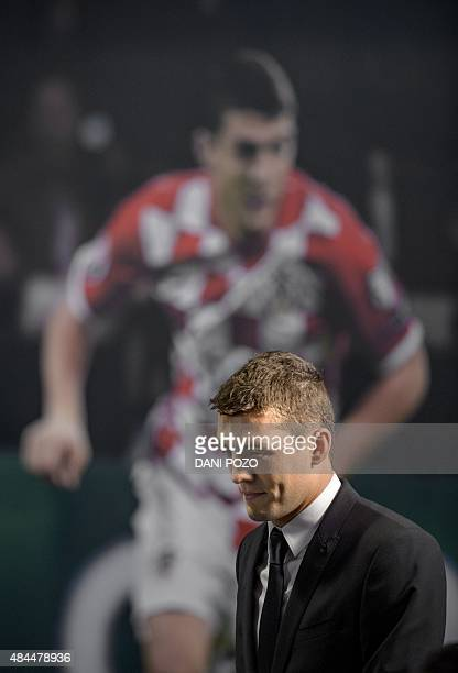 Real Madrid's new player Croatian Mateo Kovacic walks past a photograph of himself during his official presentation at the Santiago Bernabeu stadium...